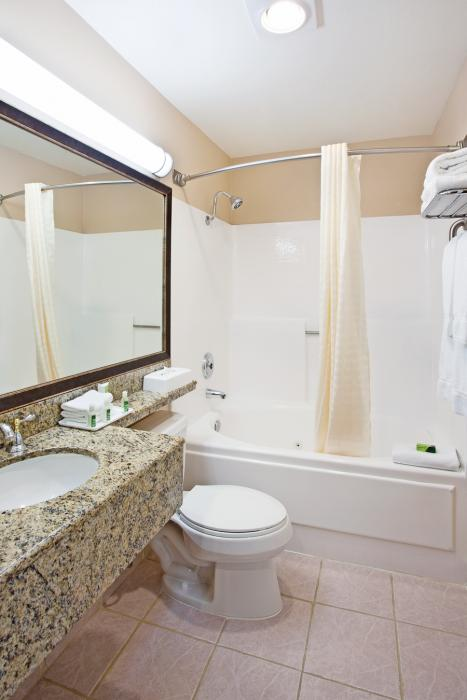Guestroom bathroom with counter, sink, toilet and bathtub