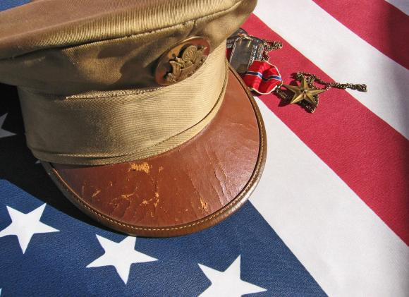 Military cap placed respectfully on an American flag